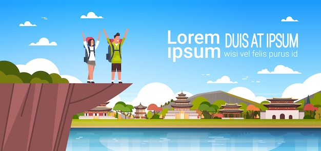 Couple of cheerful tourists with backpacks over beautiful chinese buildings background with copy space man and woman hikers