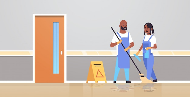 Couple cleaners in uniform working together cleaning service concept   man woman janitors using mop spray plastic bottle modern clinic corridor interior full length