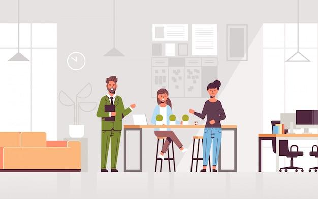 カップルの同僚がチームのモダンなコワーキングセンターオフィスインテリアに採用された労働者を紹介する新しい女性従業員を指しています。