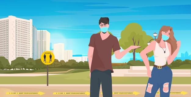 コロナウイルスの社会的距離の概念都市の景観の背景の水平方向の肖像画を防ぐために距離を保つ公園での会議中に話し合うカップル