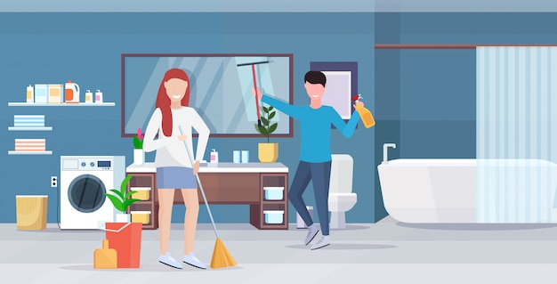 Couple doing housework together man wiping glass mirror woman sweeping floor with broom cleaning housekeeping concept modern bathroom interior full length horizontal