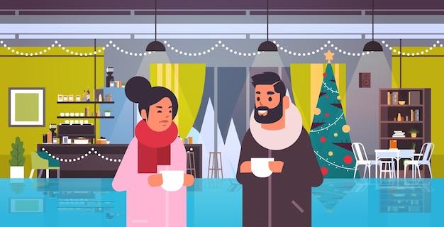 コーヒーを飲み、装飾されたモミの木とレストランでの会議中に話し合うカップルメリークリスマス明けましておめでとうございます冬の休日のコンセプトモダンなカフェのインテリア