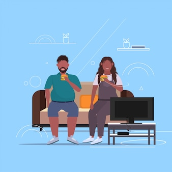 Couple eating hamburger fast food overweight   man woman watching tv sitting on couch unhealthy lifestyle obesity concept full length