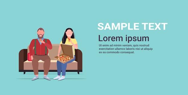 Пара есть пицца фаст-фуд избыточный вес мужчина женщина сидя на диване нездоровое питание ожирение концепция полная длина горизонтальный