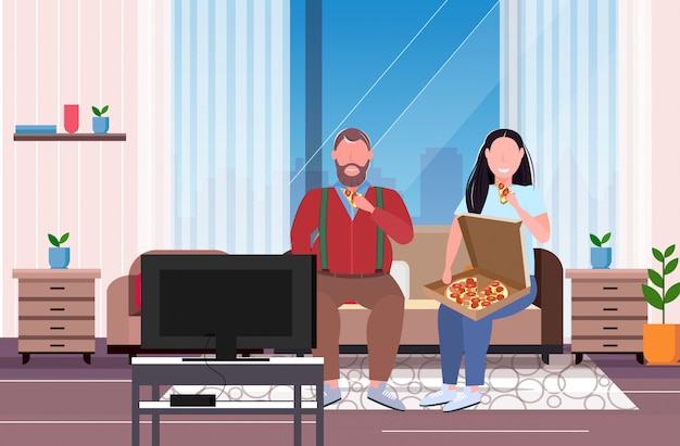 Couple eating pizza fast food overweight man woman watching tv sitting on couch unhealthy nutrition obesity concept modern living room interior full length  horizontal