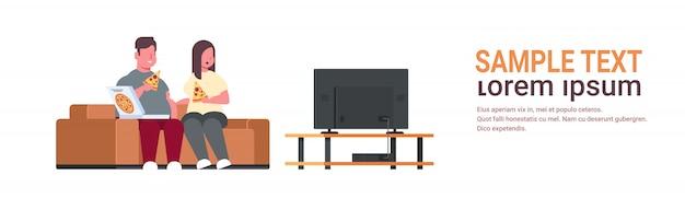 Пара ест пиццу мужчина женщина смотрит телевизор сидя на диване нездоровый фаст-фуд концепция ожирения полностью