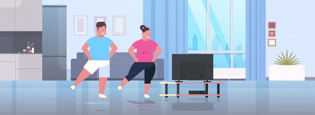 カップルはテレビ番組中に運動男性女性フィットネスプログラムホームトレーニングを見ながらトレーニング