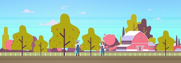 木から梨を選ぶカップルの農家男性熟した果実を収穫する女性庭師庭の農業農地の田舎の風景に収穫を集める