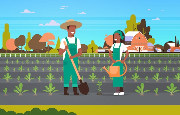 Couple farmers planting seedlings plants vegetables   man woman gardeners using shovel watering can eco farming concept farmland countryside landscape horizontal