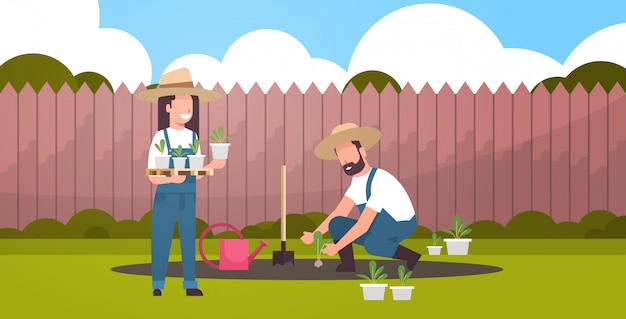 Couple farmers planting young seedlings plants flowers and vegetables man woman working in garden eco farming concept backyard background flat full length horizontal