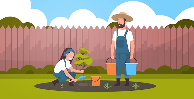 Couple farmers planting young tree man holding water buckets woman digging soil working in garden agricultural gardening concept backyard background flat full length horizontal