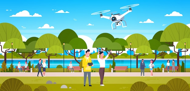 Couple flying drone in park man and woman using remote controller play with copter outdoors