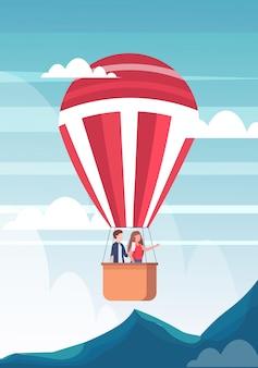 뭔가 여행 개념 산 풍경 배경 평면 수직 손을 가리키는 스마트 폰 카메라 여자에 사진을 복용 뜨거운 공기 풍선 남자의 바구니에 비행 커플