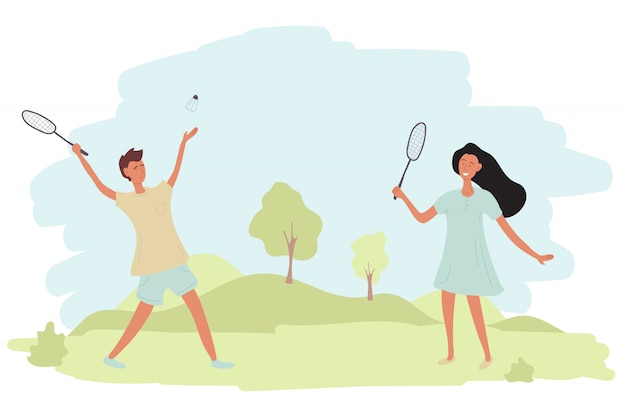 A couple a guy and a girl are playing badminton outdoors.