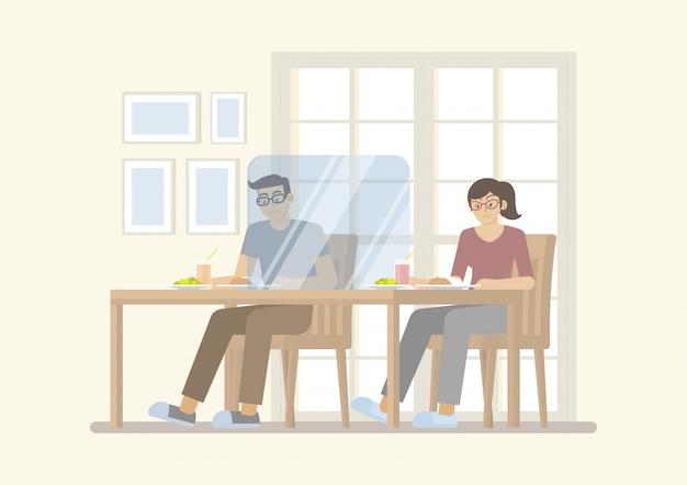 Пары имея еду на таблице с прозрачной перегородкой в ресторане для новой нормальной концепции