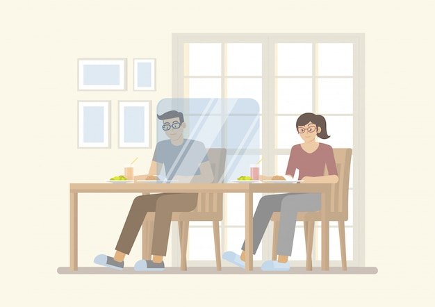 Couple having meal on table with transparent partition in restaurant for new normal concept