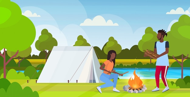 Couple hikers making fire man woman holding firewood for bonfire hiking concept african american travelers on hike tent camping nature landscape background horizontal full length flat