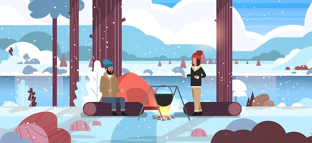 Couple hikers man woman cooking meals in bowler boiling pot at campfire near camp tent camping concept winter landscape nature river mountains snowfall