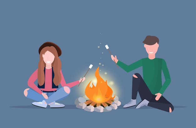 Couple hikers roasting marshmallow candies on campfire hiking camping concept man woman travelers on hike horizontal full length flat