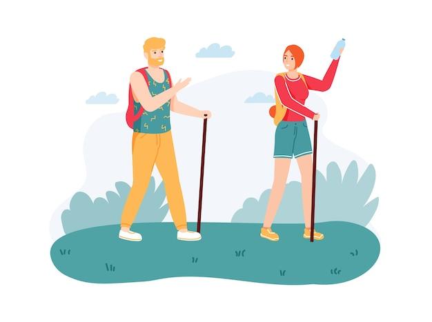杖で自然をハイキングするカップル。旅をしている機器とバックパックを持つ男と女。