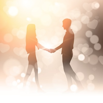 Couple hold hands over bokeh golden blur shiny light