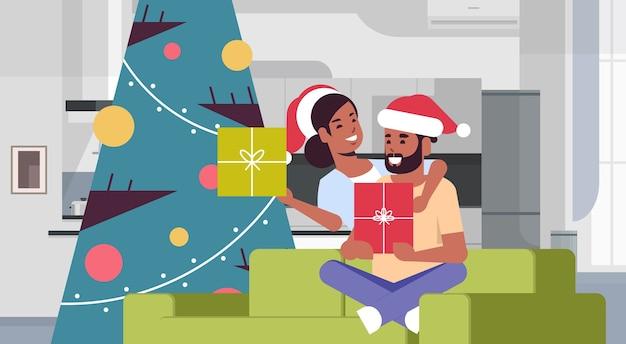 ギフトボックスを保持しているカップルメリークリスマス幸せな新年の休日のお祝いのコンセプト男性女性がフィットツリーの近くのソファに座ってサンタの帽子をかぶって抱きしめる