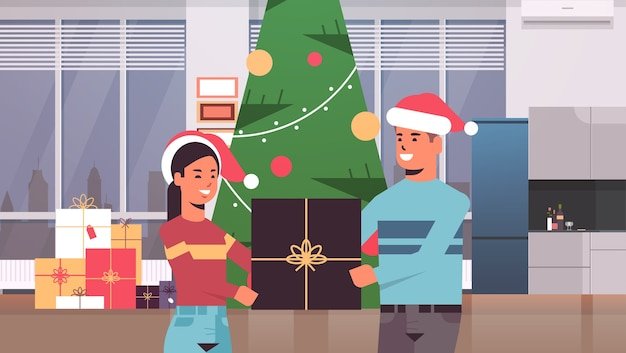 Couple holding gift present box merry christmas happy new year holiday celebration concept man woman wearing santa hats standing near fit tree modern living room interior horizontal portrait vector il
