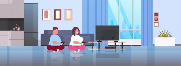 Пара держит джойстик игровой коврик семьянин женщина играющая в видеоигры на экране телевизора
