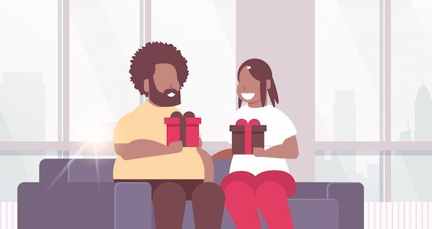 ラップされたギフトボックスを保持しているカップルの休日のお祝いのコンセプトソファに座っている男性女性