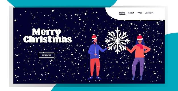 Пара в шапках санта-клауса держит снежинку счастливого рождества с новым годом зимние праздники празднование концепция мужчина женщина стоит вместе