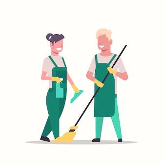 Пара уборщики мужчина женщина в униформе уборщицы держа шваброй и спрей пластиковая бутылка работают вместе