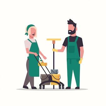 Пара дворники мужчина женщина в униформе работает вместе с профессиональным оборудованием уборщицы толкают тележку тележки с инструментами