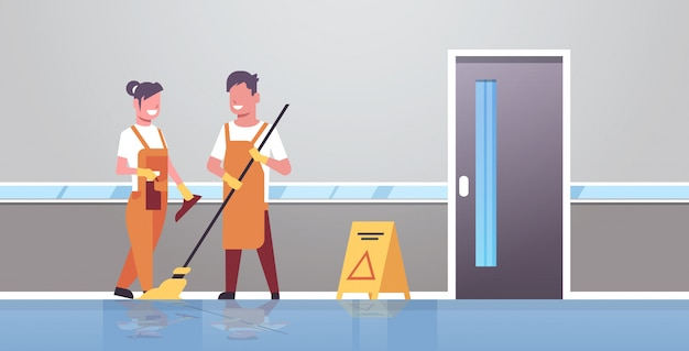Couple janitors man woman in uniform cleaning service cleaners holding mop spray plastic bottle working together modern clinic corridor interior