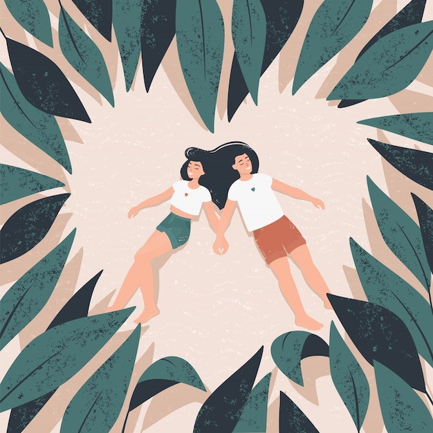 A couple in love lies on the sand surrounded by tropical leaves in the shape of a heart