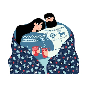 Couple in matching sweaters sitting together with warm cup under holiday blanket