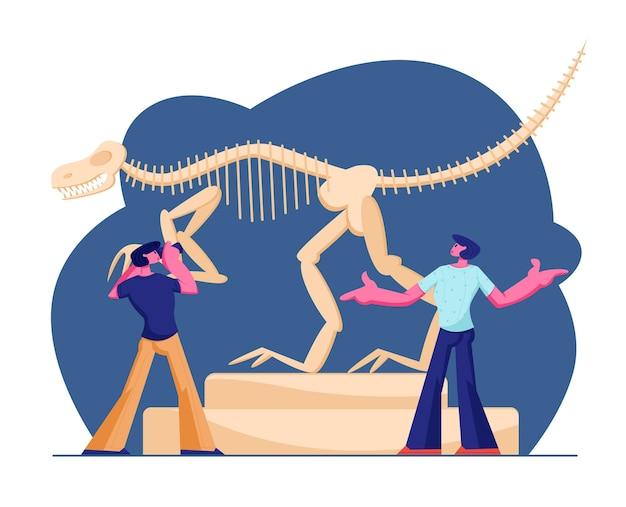 Couple of men visiting paleontology museum, making photo of huge tyrannosaur rex bones in museum exhibition