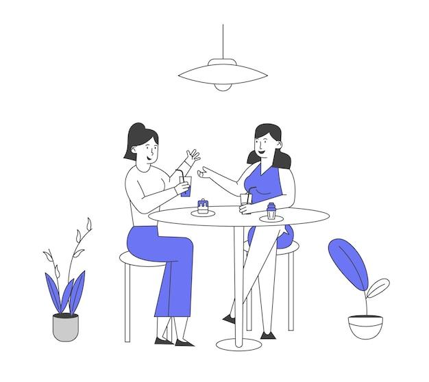Пара подружек, сидящих за столом с едой и напитками и общающихся