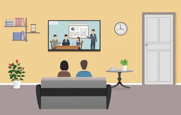リビングルームのインテリアでテレビを見ている男女のカップル。家族はテレビの前のソファーでリラックスします。