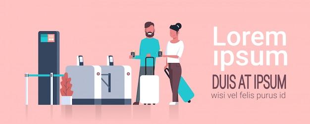 登録のためにセキュリティスキャナーを通過する空港でチェックインスーツケースを持って観光客のカップル