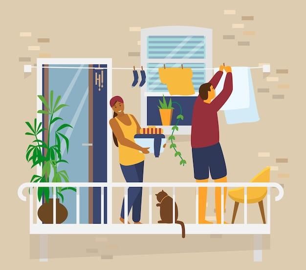 Пара на балконе вешает белье. домашние мероприятия. внешний вид кирпичного дома. плоский
