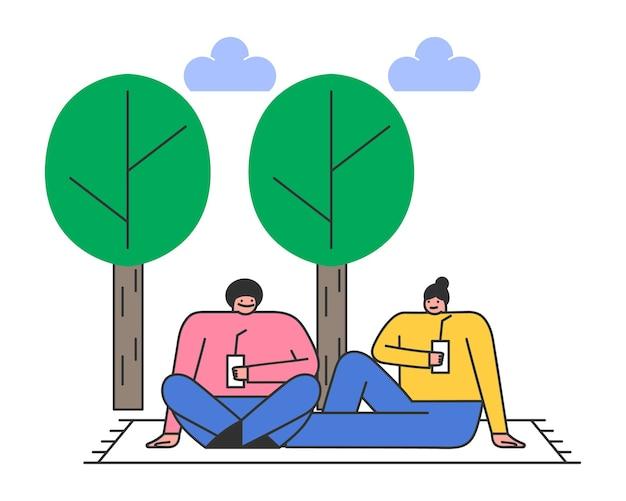 공원에서 피크닉에 커플. 남자와여자가 나무 아래 잔디에 담요에 앉아