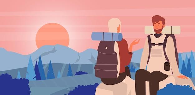 Пара людей наслаждается закатом в горном пейзаже, туристы-туристы, сидящие на камнях