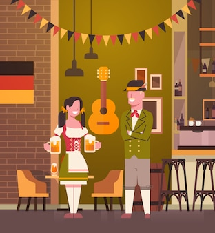 Couple in pub wearing traditional clothes drink beer in bar oktoberfest party celebration man and woman fest concept