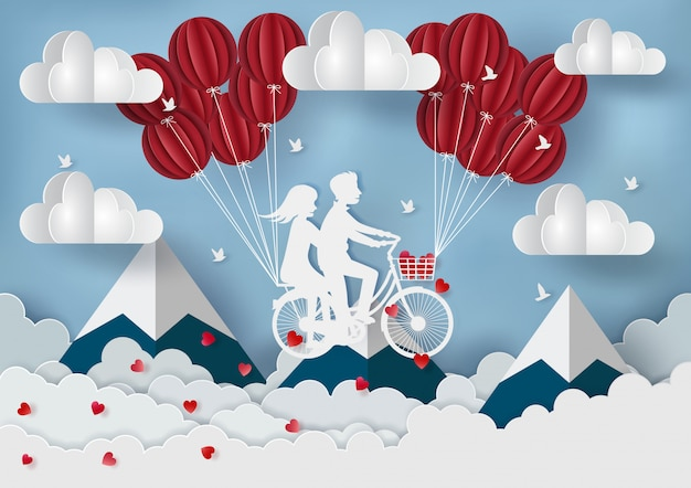 Couple riding a bicycle with red balloons above the mountains