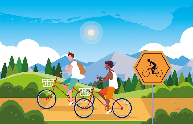 Couple riding bike in landscape with signage for cyclist