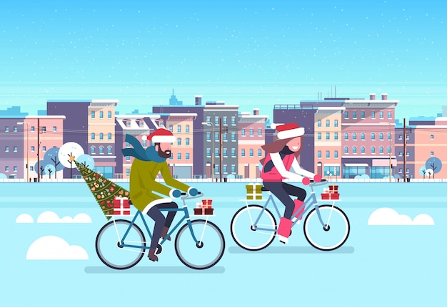 Couple riding bike with fir tree gift box over city street buildings cityscape