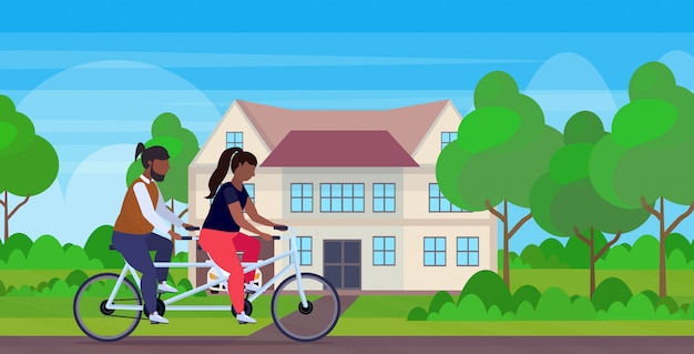 Couple riding tandem bike african american overweight man woman cycling twin bicycle together workout weight loss concept villa house landscape background full length