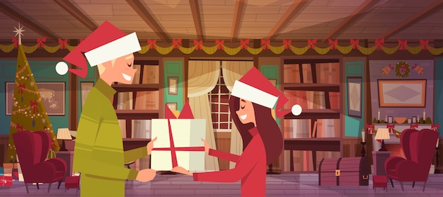 Couple in santa hats holding present box celebrate christmas together at home, cute man and woman greeting happy new year poster design