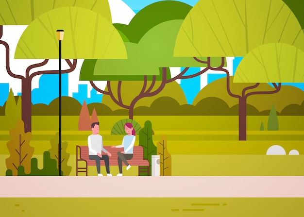 Couple sit on bench in city park talking man and woman relaxing in nature communicating