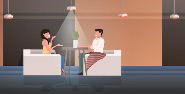 Пара сидит за столом в кафе и обсуждает романтическое свидание